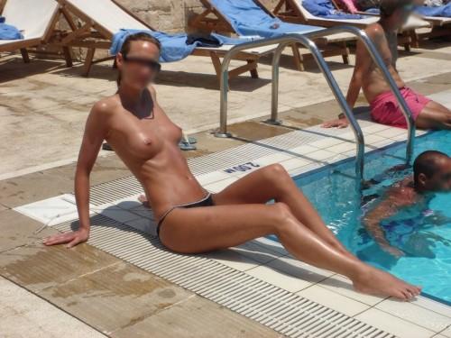 une femme topless à la piscine