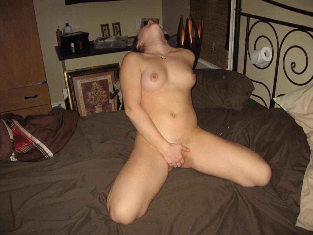 Une amatrice nue aux beaux nichons se masturbe sur son lit